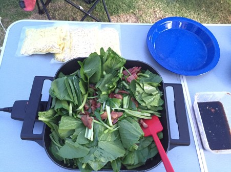 add noodles and sauce to fried pork and greens