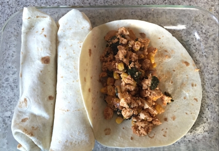 scoop tofu filling into tortillas and roll up